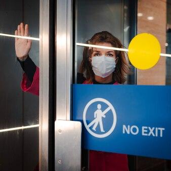 Pare a infecção. mulher mostra gesto de parada pela porta de vidro, não há saída. garota usa uma máscara protetora contra doenças infecciosas gripe em um local público.