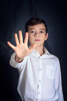 Pare a mão de um menino como sinal de discriminação ou um símbolo violento de violência com um fundo de tom escuro.