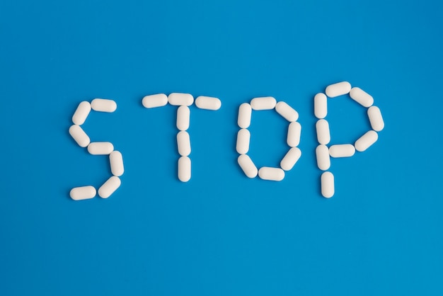Pare a palavra feita dos comprimidos brancos no fundo azul. foto do conceito de vista superior