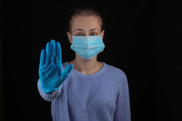 Pare a pandemia de covid-19. mulher com máscara médica em uma parede preta