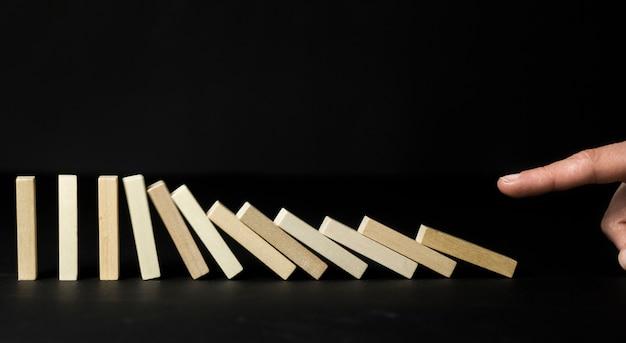 Pare a queda contínua dos dominós, contra um fundo preto. pare a queda do ônibus
