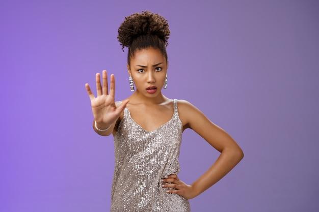Pare aí mesmo. mulher afro-americana preocupada, insegura e preocupada, implorando o suficiente estender a palma levantada gesto de tabu suficiente segurar a cintura da mão franzindo a testa exigindo proibir, fundo azul.
