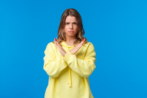 Pare aí, não significa não. mulher loira confiante de aparência séria com capuz amarelo fazendo cruz no peito, suficiente e recusar o gesto, procura parar, ficar