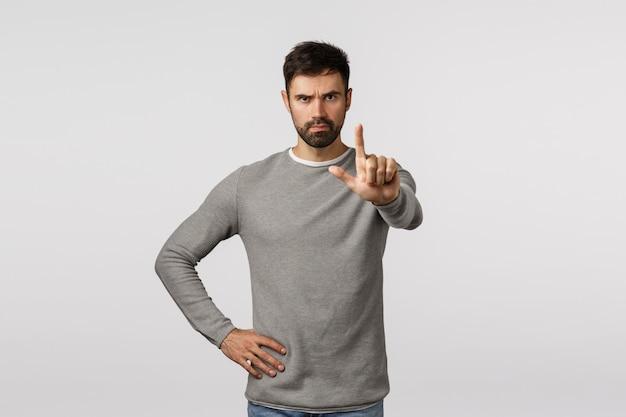 Pare aqui. suficiente. o amigo barbudo determinado e confiante de aparência séria avisa o parceiro, estende o dedo indicador e sacode-o com restrição, proíbe, proíbe a ação, fica em pé