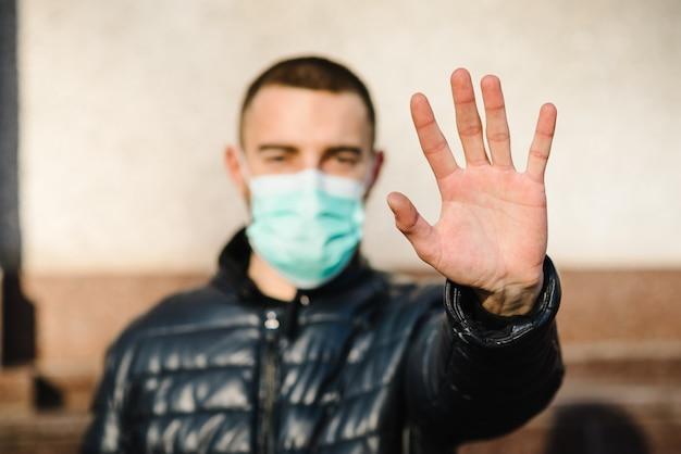 Pare as doenças epidêmicas do vírus. coronavírus. homem saudável na máscara protetora médica, mostrando a parada do gesto. proteção e prevenção da saúde durante a gripe e surtos infecciosos.