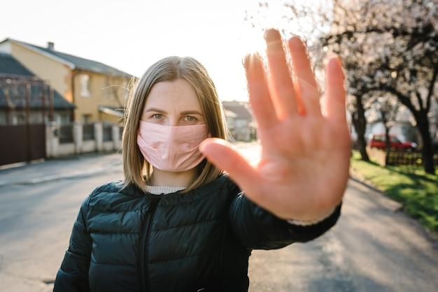 Pare as doenças epidêmicas do vírus. coronavírus. uma mulher saudável em uma máscara protetora médica mostrando uma parada de gesto na rua. proteção e prevenção da saúde durante a gripe, surto infeccioso. país.