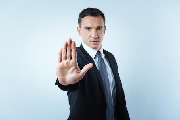 Pare com isso. homem bonito sério olhando para você e mostrando a palma da mão enquanto manda parar