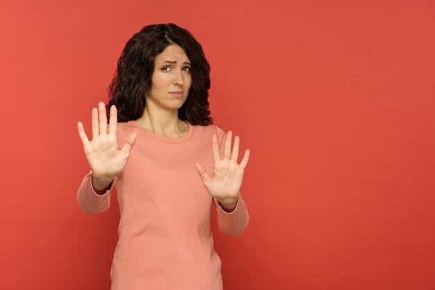 Pare com isso, mulher com recusa ou negação, gesto de mão com expressão de nojo ou rosto assustado no vermelho