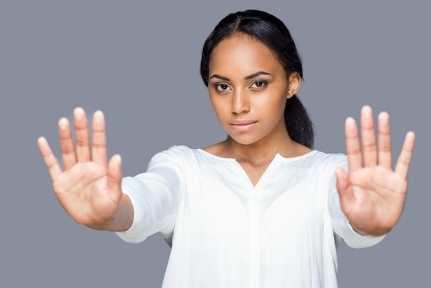 Pare com isso! mulher jovem e atraente africana mostrando as palmas das mãos, mantendo as mãos estendidas e em pé contra um fundo cinza