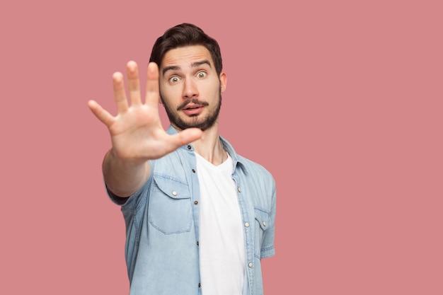 Pare com isso. retrato de jovem barbudo bonito chocado em pé de camisa azul estilo casual com sinal de mão parada e olhando para a câmera. tiro de estúdio interno, isolado no fundo rosa.