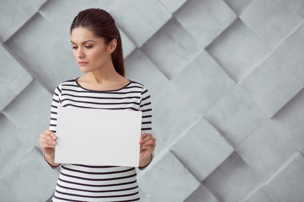 Pare de assédio. mulher agradável e agradável e triste em pé contra a parede e olhando para o lado enquanto mostra o slogan