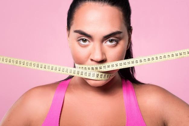 Pare de comer. feche o retrato da senhora mulata gordinha cobrindo a boca com a fita métrica de corpo.