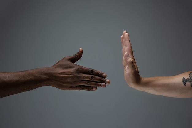 Pare de envergonhar. tolerância racial. respeite a unidade social. mãos africanas e caucasianas, gesticulando no fundo cinza do estúdio. direitos humanos, amizade, conceito de unidade internacional. unidade inter-racial.