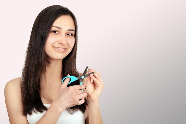 Pare de fumar conceito. a jovem mulher cortou cigarros com sorriso feliz das tesouras. foco na mão, tesouras e cigarros