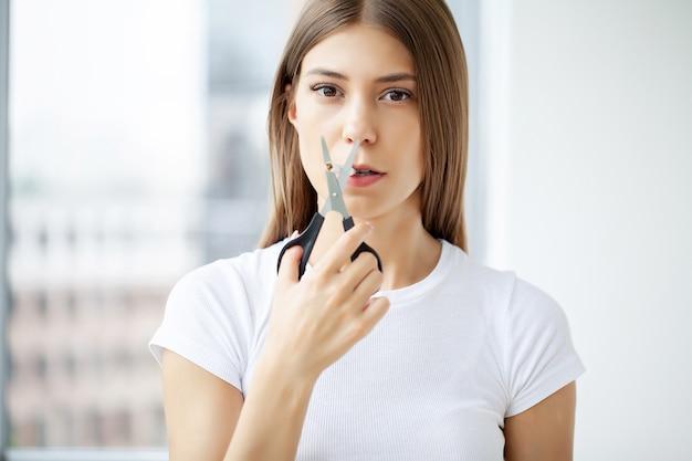 Pare de fumar, jovem corta um cigarro com uma tesoura.