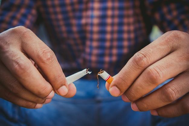Pare de fumar, mãos humanas, quebrando o cigarro