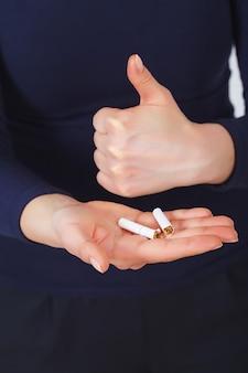 Pare de fumar. mulher bonita quebrando cigarro pela metade