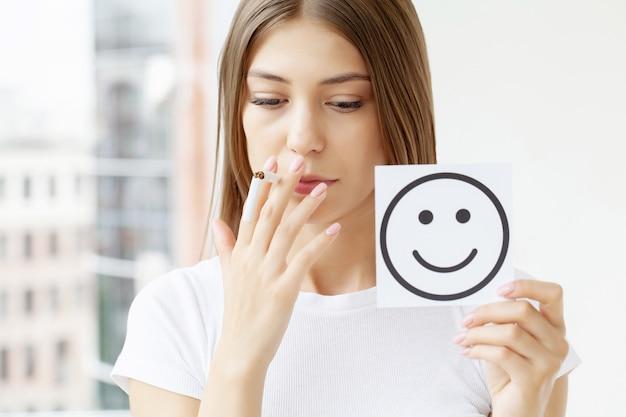 Pare de fumar, mulher segurando um cigarro quebrado e um cartão com um sorriso