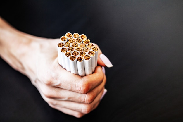 Pare de fumar o conceito no fundo com cigarros quebrados. monte de cigarros. proibido fumar