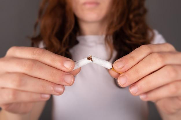 Pare de fumar o sinal, cigarro quebrado nas mãos de uma mulher.