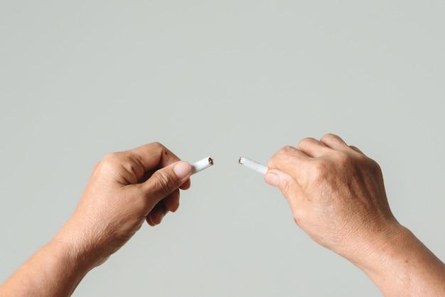 Pare de fumar, sem dia de fumo, mãos da mãe quebrando o cigarro