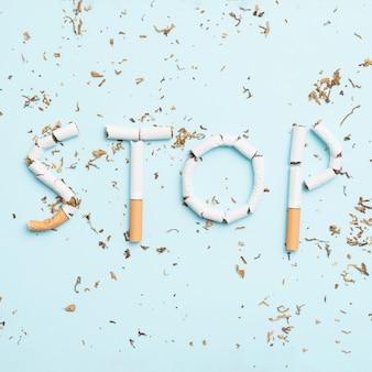 Pare de fumar texto feito com cigarro quebrado e tabaco em fundo azul