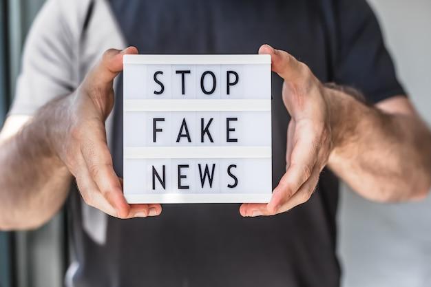 Pare de infodemias de notícias falsas. homem com as mãos segurando uma mesa de luz com o texto pare de notícias falsas