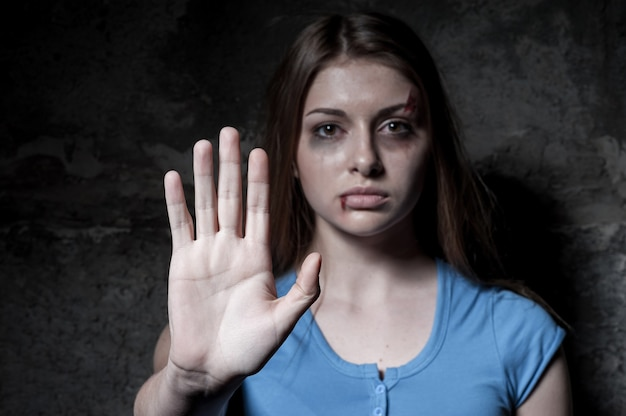 Pare de machucar mulher! jovem espancada olhando para a câmera e esticando a mão enquanto fica de pé contra uma parede escura