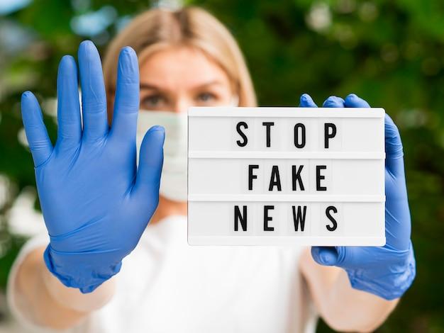 Pare de notícias falsas turva mulher usando luvas