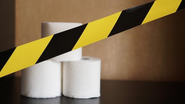 Pare de pânico - coronavírus. rolos de papel higiênico atrás da fita amarela