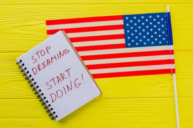 Pare de sonhar, comece a fazer. slogan de motivação escrito no bloco de notas com a bandeira dos estados unidos na mesa de madeira amarela.