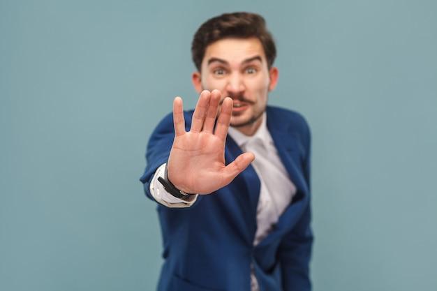 Pare. empresário mostrando proibição de mão na câmera. conceito de pessoas de negócios, ricamente e sucesso. interior, estúdio filmado em fundo azul claro