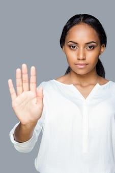 Pare! mulher jovem e atraente africana mostrando a palma da mão, mantendo a mão estendida e em pé contra um fundo cinza