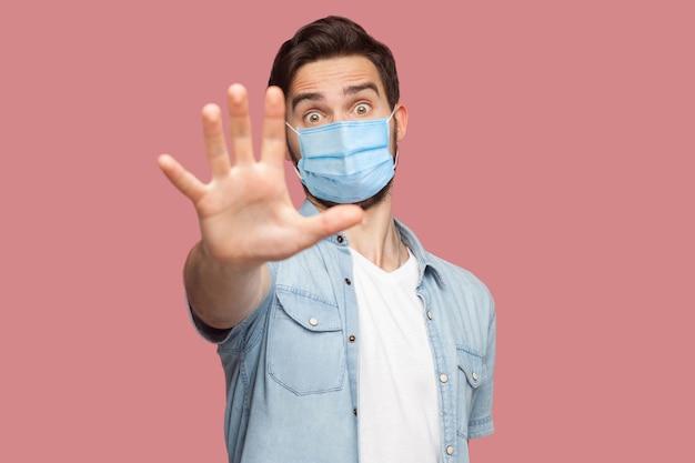 Pare, não se aproxime. . retrato de jovem bravo com máscara médica cirúrgica na camisa azul em pé com sinal de mão parada e olhando para a câmera. tiro de estúdio interno, isolado no fundo rosa.