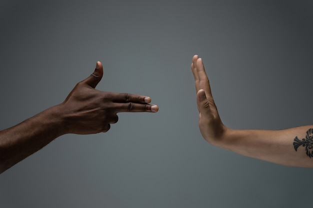 Pare negativo. tolerância racial. respeite a unidade social. mãos africanas e caucasianas, gesticulando no fundo cinza do estúdio. direitos humanos, amizade, conceito de unidade internacional. unidade inter-racial.