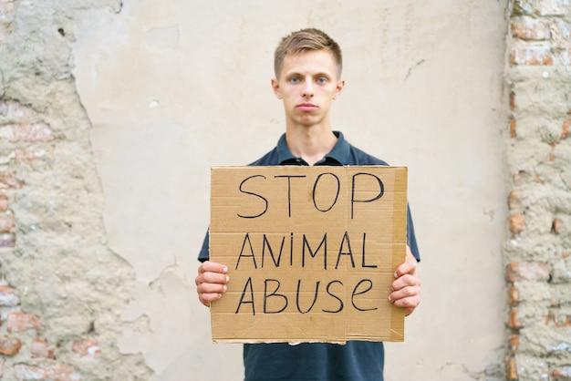 Pare o cara de abuso animal segurando uma caixa de papelão com a inscrição ativista animal caucasiano jovem m.
