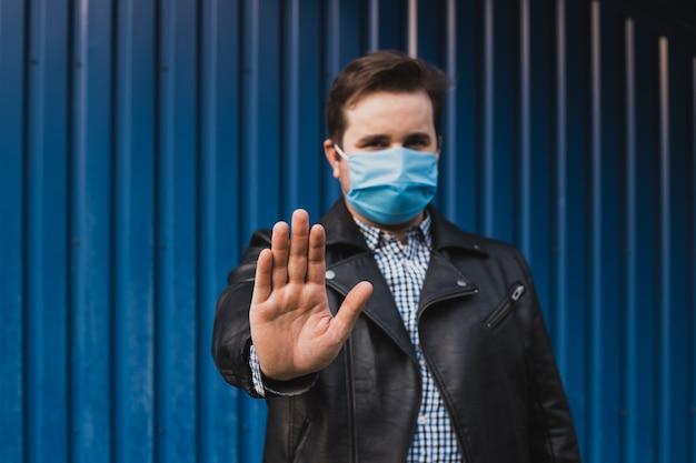 Pare o coronavírus. homem mostrando a parada do gesto. homem usa máscara protetora contra doenças infecciosas e gripe. conceito de cuidados de saúde. quarentena de coronavírus.