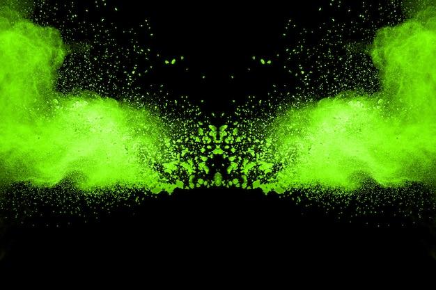 Pare o movimento do verde em pó no fundo preto. verde explosivo do pó no fundo preto.