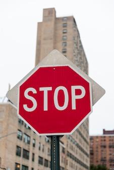 Pare o sinal de estrada com fundo edifício turva