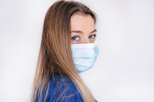 Pare o vírus e as doenças epidêmicas. mulher saudável na máscara protetora médica azul, mostrando a parada do gesto. proteção e prevenção da saúde durante a gripe e surto infeccioso