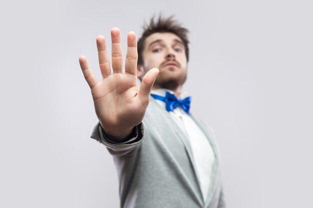 Pare. retrato de homem barbudo bonito sério em terno cinza casual, gravata borboleta azul em pé com rejeitando a mão parada e tentar bloquear ou ignorar. tiro de estúdio interno, isolado em fundo cinza claro.
