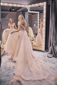 Parece certo. comprimento total de uma jovem atraente experimentando um vestido de noiva em frente ao espelho em uma loja de noivas