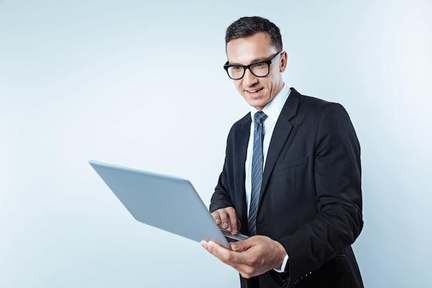 Parece interessante. cintura para cima foto de um homem de negócios concentrado focando sua atenção em uma tela de seu computador enquanto lê algo interessante sobre o fundo.