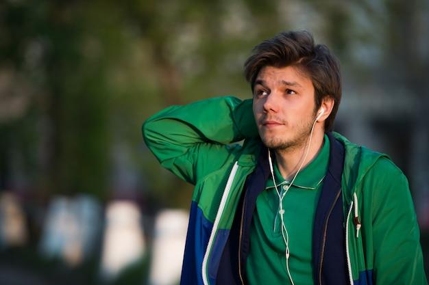 Parece jovem andando pela cidade, ouvindo música com fones de ouvido e sorrindo. close-up tiro. pôr do sol. clima de outono.