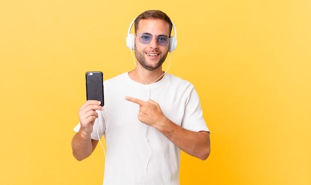 Parecendo animado e surpreso apontando para o lado, ouvindo música com fones de ouvido e um smartphone