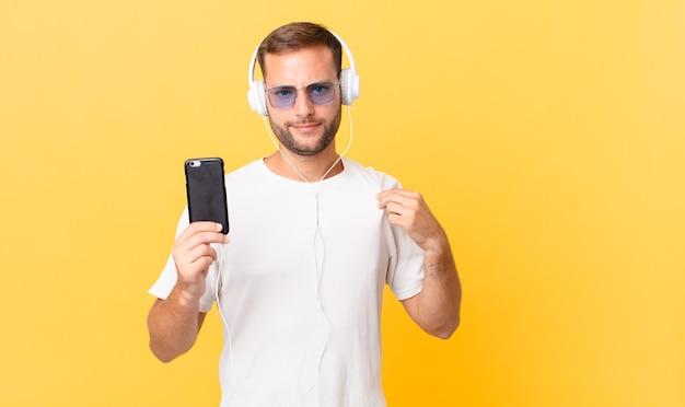 Parecendo arrogante, bem-sucedido, positivo e orgulhoso, ouvindo música com fones de ouvido e um smartphone