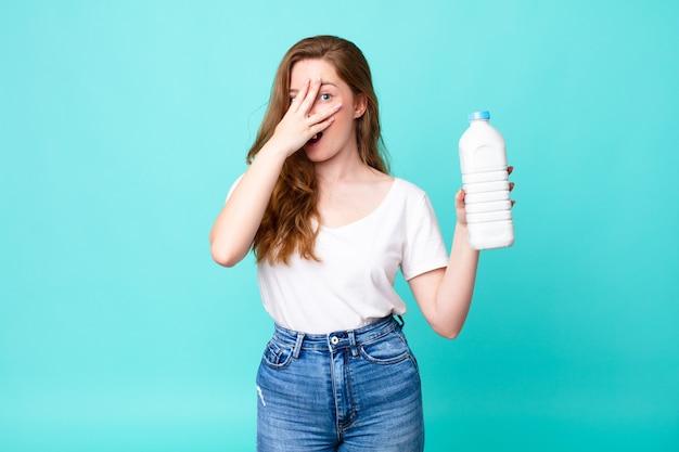 Parecendo chocado, assustado ou apavorado, cobrindo o rosto com a mão e segurando uma garrafa de leite