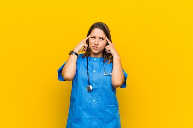 Parecendo concentrado e pensando seriamente em uma idéia, imaginando uma solução para um desafio ou problema isolado contra a parede amarela