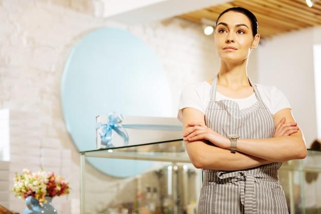 Parecendo confiante. confeiteira profissional talentosa em pé em um café com o braço cruzado e olhando pensativamente para a distância