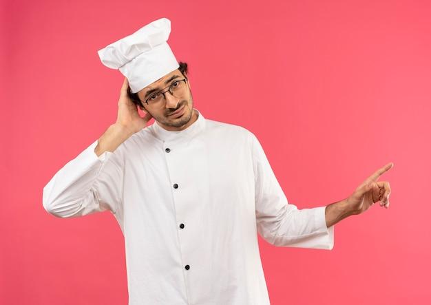Parecendo confuso, jovem cozinheiro vestindo uniforme de chef e óculos colocando a mão na cabeça e apontando para os lados